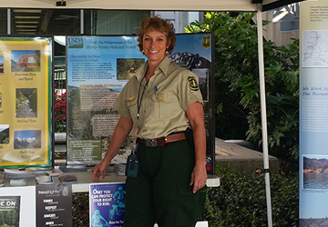 Park ranger in front of table display